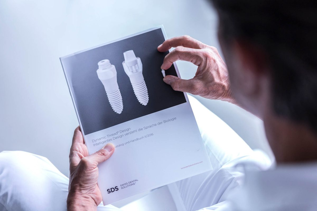 Un homme avec la brochure de SDS Swiss Dental Solutions.